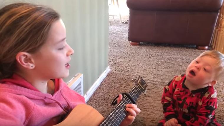 niña cantando a su hermano sindrome de down